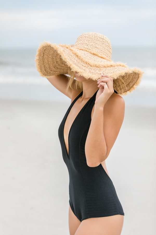 Woman in a stylish black bathing suit and hat at the beach